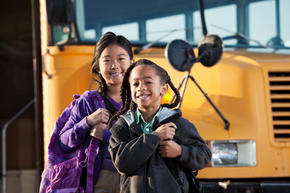 Two students near a school bus