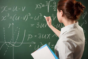 Girl solving math equation at chalkboard.