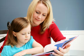 Teacher reading book with young student