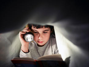 boy reading in a fort