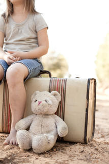 girl sitting on suitcase with stuffed animal