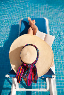 Woman lounging by the pool reading a book